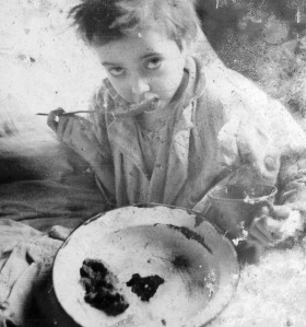 Jewish boy eating in unsanitary conditions of the Lodz ghetto